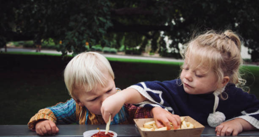 two kids eating together