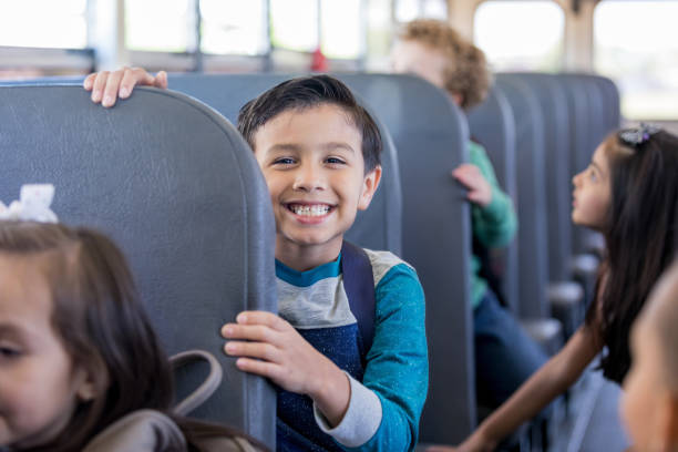 While sitting on the school bus with other children, a young schoolboy smiles with anticipation at the camera.