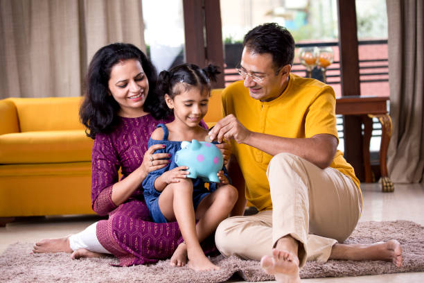 Happy parents with child inserting coin into piggy bank