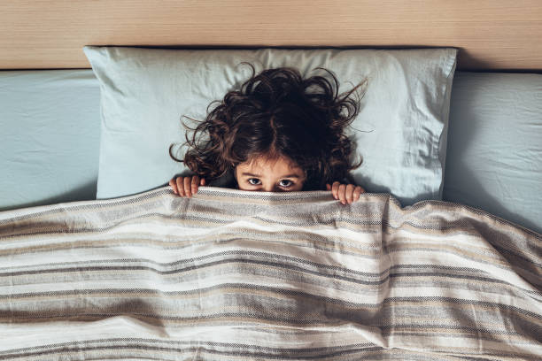 little girl covering her face with a bed sheet while sleeping