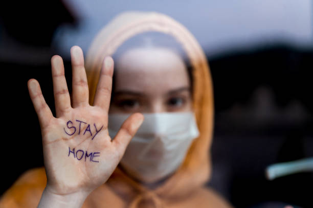 girl with yellow hoodie and a surgical mask standing and looking through the window and showing 'stay home' message written on her hand.