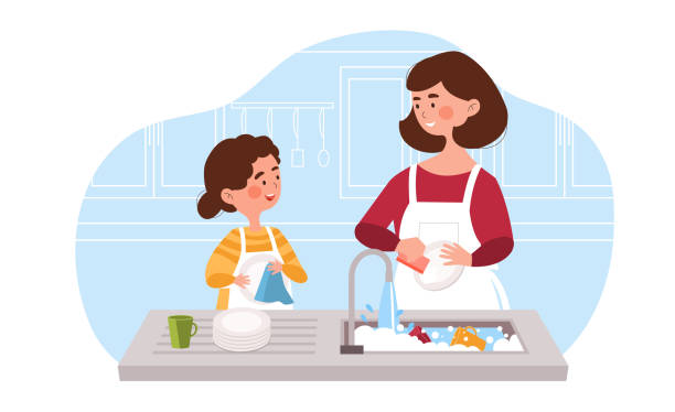 Little daughter helping her young mother to wash the dishes in the kitchen.
